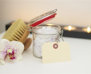 A jar of white scrub product, with a brush and an orchid flower head.