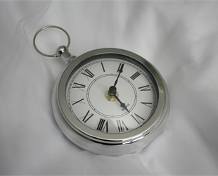 a silver clock on a white sheet